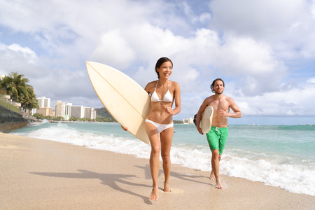 Hawaii Waikiki beach surfers having fun going surfing. Multiracial couple running out of water with surfboards after surf lesson. Stock Photo