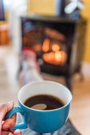 집에서 벽난로 편안 하 게 커피를 마시는 아늑한가 라이프 스타일 여자. 추운 겨울이나 가을 시즌. 집 난방 안락한 실내.