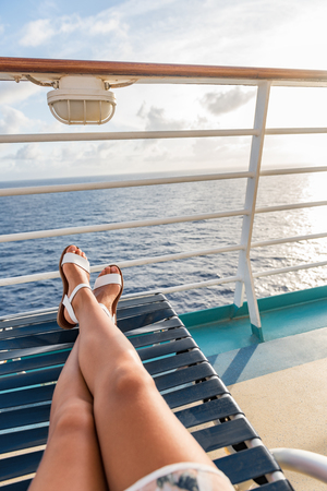 Cruise ship travel woman relaxing sun tanning onboard on deck balcony lying down on lounger chair with feet and legs up. Banque d'images