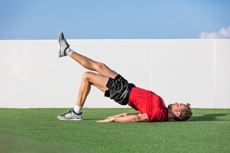 Homem da aptidão que faz exercícios do elevador de ponte do assoalho do único pé do glute do peso corporal. O atleta apto que treina os músculos dos glutes com a extremidade de uma perna do assoalho levanta a extremidade no gym exterior do verão na grama. Foto de archivo