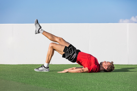 Fitness man doing bodyweight glute single leg floor bridge lift exercises. Fit athlete training glutes muscles with one-legged floor bridge butt raise in summer outdoor gym on grass.
