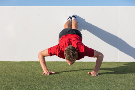 Push up fitness man training using wall doing decline pushup at outdoor gym. Male fitness athlete doing advanced push-ups on grass park. Stock Photo