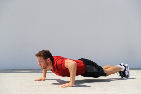 Pushup fitness man doing push-up bodyweight exercise on gym floor. Athlete working out chest muscles strength training outdoors