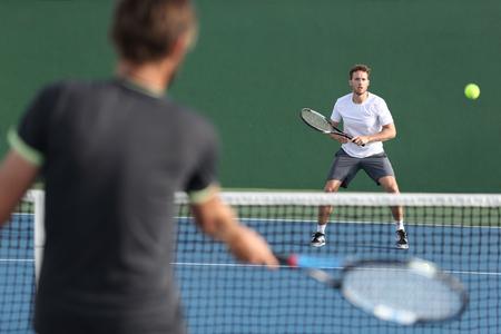Gli uomini sfoggiano atleti giocatori che giocano a tennis insieme. Due tennisti professionisti che colpiscono la palla sul campo all'aperto duro durante il gioco. Archivio Fotografico - 90920624