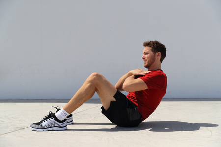 Fitness man doing sit-ups bodyweight floor exercises at gym. Sport athlete doing exercise training abs muscles doing crunches working out to get six pack.