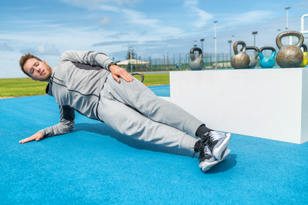 Planking fitness man doing side plank exercises at outdoor gym training obliques muscles on floor. Bodyweight workout outside at athletics stadium.