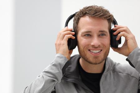 Homem colocando em fones de ouvido para ouvir música celular app. Os auriculares vestindo de sorriso felizes da pessoa urbana nova cantam o app móvel do smartphone que escuta músicas na sala de visitas em casa.