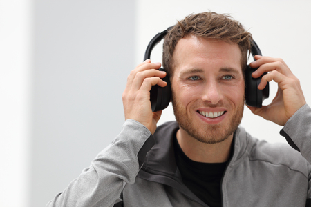 Man putting on headphones to listen to music mobile phone app. Happy smiling young urban person wearing headset sing smartphone mobile app listening to songs in living room at home.