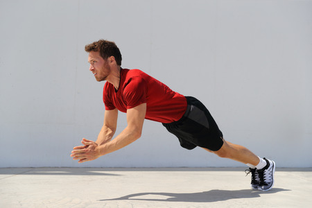 Clap pushup fitness man doing plyometrics push-up explosive workout for muscles training. Athlete working out on gym floor.