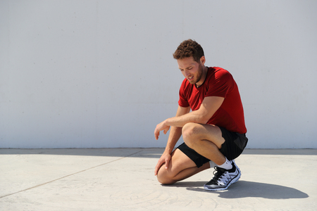 Tired sport fitness man exhausted breathing after difficult workout outdoors. Heat exhaustion athlete dehydrated or runner with knee injury pain resting in disappointment. Stock Photo