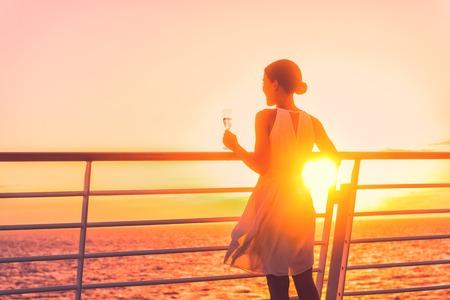 Luxe cruiseschip reizen elegante vrouw drinken glas champagne genieten van kijken naar zonsondergang vanaf het bootdek over de oceaan in Europa bestemming vakantie. Cruisen zeilen weg op vakantie. Stockfoto