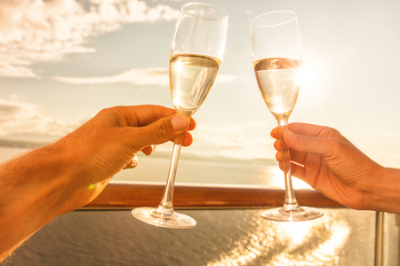 Luxury cruise ship travel couple toasting champagne glasses for celebration honeymoon. Caribbean holiday drinking doing cheers at sunset view sun flare of cruise holiday destination.