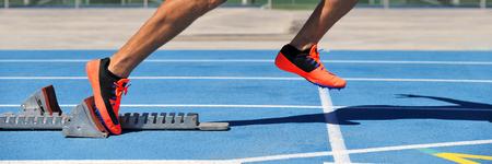 Pista os pés das sapatas dos pontos em blocos começar na pista de atletismo e nas pistas azuis do estádio do campo. Corredor do atleta do homem de Sprinting no começo da corrida que sae no início da competição da raça. Colheita de banner.