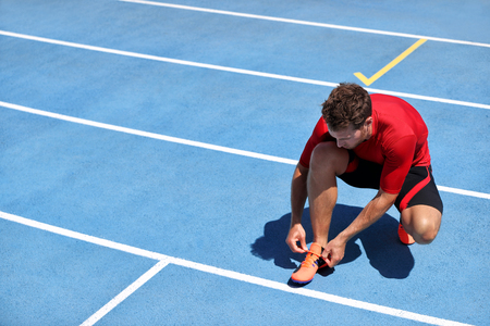 Athlete sprinter getting ready to run tying up shoe laces on stadium running tracks. Man runner preparing for race marathon training outdoors. Fitness and sports. Stock Photo