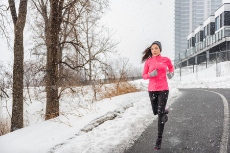Winter running Asian girl wearing cold weather clothing for outside exercise in snow storm snowfall during winter training outdoors in city street. Fitness woman exercising.
