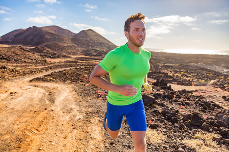 Trail runner running man. Sports and fitness concept. Male athlete ultra running in nature mountain path. Active fit sport man in compression clothing on rocks working out cardio training body.