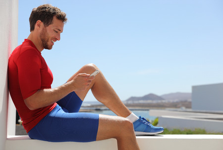 Fitness sport man using mobile phone app after workout training relaxing sitting at home balcony. Technology and sports athlete holding smartphone. Active and healthy lifestyle.
