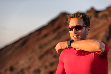 Technology for sport and active living. Athlete man talking into smartwatch wearable tech device speaking to someone or dictating message on smart watch app. Fitness lifestyle.