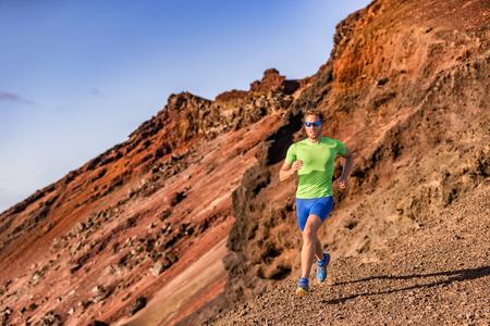自然の中で山の岩道で走るトレイルランナーマンアスリートウルトラ。火山の山のバックカントリー風景。フィットネスとスポーツのアクティブな
