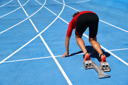Runner ready to run on running track start line. Sport athlete going sprinting towards success on blue tracks. Sprinter on competition race challenge at stadium. Stock Photo