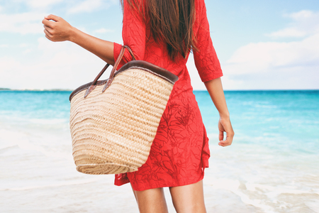 Beach bag vacation woman walking carrying things on tropical holidays holding tote purse for summer accessories for the beach. Tourist walking with red beachwear dress on travel holidays.