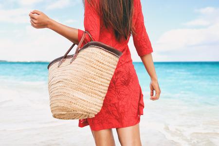 Strandtas vakantievrouw lopen dragende dingen op tropische vakantie met tote portemonnee voor zomer accessoires voor het strand. Toerist die met rode strandkledingkleding op reisvakanties loopt.