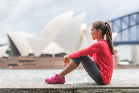 Sydney city woman living an active lifestyle relaxing at urban park after running cardio exercise outside in summer. Asian girl sitting with Sydney tourist attraction in background.
