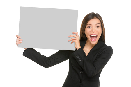 White sign happy Asian business woman holding blank card isolated on white background in studio portrait. Screaming excited Chinese businesswoman showing empty poster with copy space for text advert.