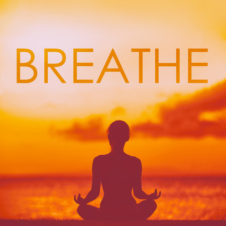 BREATHE yoga inspirational title on beautiful beach with woman meditating doing yoga at sunset. Word breathe written on copy space for inspiration and motivation in health and fitness concepts. Stock Photo