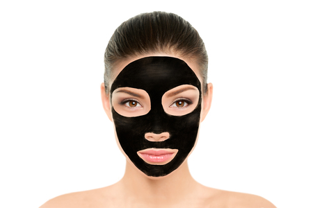 Black charcoal mask facial treatment Asian beauty woman. Wellness and spa purifying peel off mask face portrait, isolated on white background. Cleansing skin care to remove blackheads and clean pores. Stock Photo