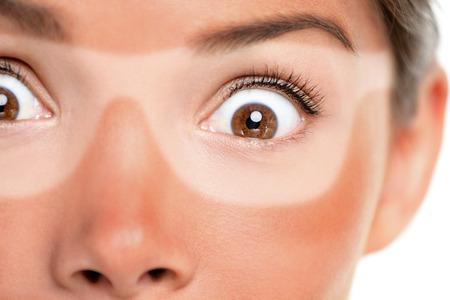 Sonnenbrandbräunliche Sonnenbrillen, rote, schmerzende Haut. Die erschrockene Asiatin, die mit lustigem Ausdruck entsetzt wurde, vergaß, Lichtschutz auf Gesicht auf Sommerferien zu setzen. Sonnenbräunehautkrebs-Gesichtspflegekonzept. Standard-Bild