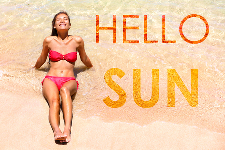Graphic design inspirational quote creative concept with the words HELLO SUN! written on water background. Asian bikini girl lying down in sand sunbathing in swimwear with sentence for sun holidays. Stock Photo