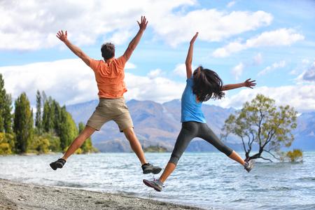 뉴질랜드 관광객 부부는 와나카 (Wanaka)의 행복에서 뛰어 오르고 있습니다. 여름 모험 목적지에서 여행하는 기쁨 관광의 재미있는 점프를 하 고  스톡 콘텐츠