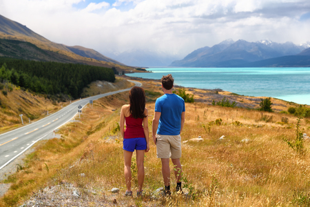 New Zealand travel nature couple tourists looking at view of AorakiMount Cook at Peters lookout, famous tourist destination. Stock Photo