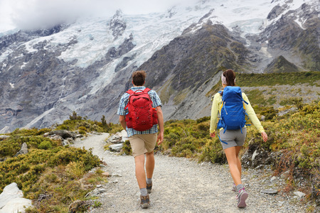 New Zealand travel tramping hikers walking on trail of Hooker Valley Track in New Zealand AorakiMt Cook. Couple tourists hiking in mountains on popular tourist destination. Kiwi trampers with bags.