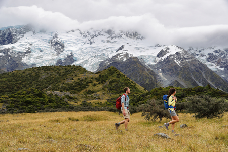 New Zealand travel hikers hiking on snow capped mountains landscape background. Couple trampers walking on Hooker Valley Track, popular tourist destination for summer vacation.