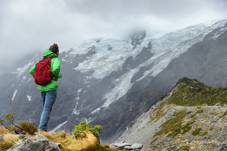 New Zealand hiker man hiking, enjoying view of snow capped mountain landscape in Hooker Valley track. Alps alpine background Active hiker standing . Mountaineering sport lifestyle. Stock Photo
