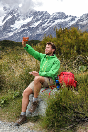 New Zealand kiwi tramper taking selfie phone picture during hike on Hooker Valley track trail in Mt Cook. Summer hiker eating lunch break during hiking. Happy man taking photos.
