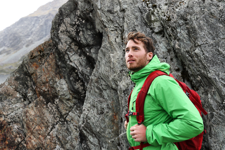 Hiker - man hiking in mountains. Adventure outdoor lifestyle. Male hiker looking to the side walking in forest. Caucasian person portrait outdoors in nature. Stock Photo