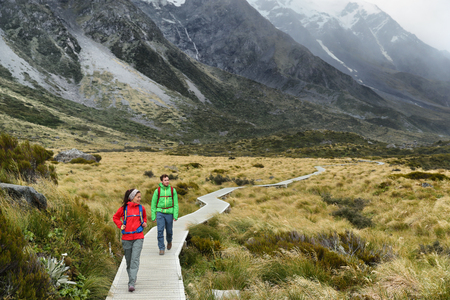 New Zealand trampers backpacking on Mount Cook  Aoraki Hooker valley travel. hikers hiking walking on Hooker Valley Track in summer on boardwalk. Couple on travel holiday adventure. Stock Photo