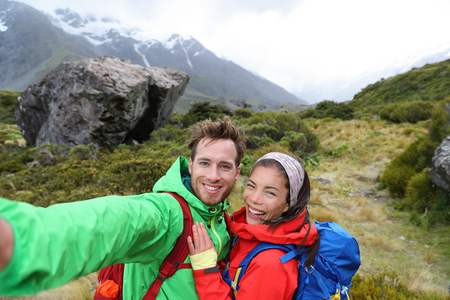 New Zealand travel selfie happy couple backpackers hiking. Travel selfie couple hikers taking smartphone picture on outdoor trail hike in outdoor nature. Active healthy happy people. Stock Photo - 92867929