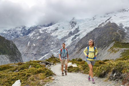 New Zealand backpackers tramping on Mount Cook  Aoraki Hooker valley travel. Backpacking hikers hiking on walking on Hooker Valley Track. Snow capped mountains glacier landscape. Couple on adventure.