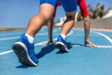 Sprinter waiting for start of race on running tracks at outdoor stadium. Sport and fitness runner man athlete on blue run track with running shoes. Stock Photo