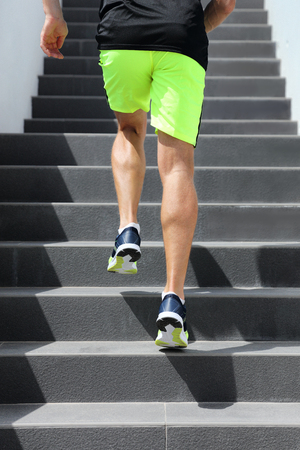 Runner man athlete running up the stairs on hiit high intensity interval training city run. Jogging jogger climbing staircase sprinting with speed. Urban active lifestyle. Closeup of legs and shoes. Stockfoto