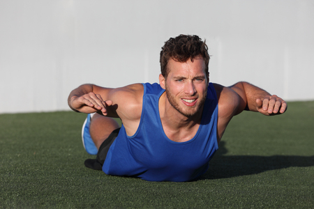 Fitness training back fat exercise fit man doing variation of lower body workout. Strong athlete working out outdoors in park grass. Lower body back lumbar muscles strengthening exercises.