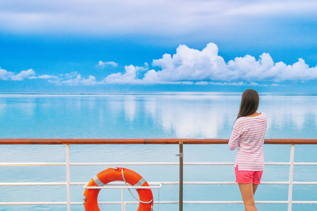 Cruise ship luxury travel woman on deck looking away in Tahiti. Serene still ocean water landscape. Tourism vacation holidays in French Polynesia. Stock Photo