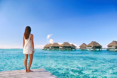 Luxury travel Tahiti vacation woman looking at overwater bungalows resort in French Polynesia. Woman on terrace deck in pristine turquoise water wearing cover-up beachwear dress relaxing. Stock Photo