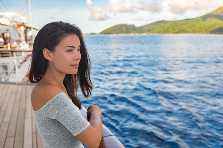 Cruise ship luxury vacation travel woman boat passenger looking at sunset from deck. Beautiful Asian girl tourist relaxing outside enjoying view.