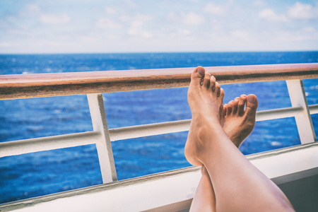 Cruise vacation travel woman relaxing with feet on balcony ship deck at view of ocean on honeymoon boat voyage destination. Relaxation lifestyle.