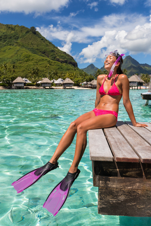 Happy vacation snorkel girl relaxing at overwater bungalow balcony at luxury resort in tahiti. Snorkeling sport activity bikini woman sun tanning in beach paradise holiday. Travel lifestyle.